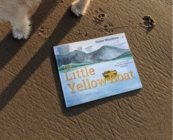 Picture of The Little Yellow Boat book by Diane Woodrow on the beach with dog paw prints above it