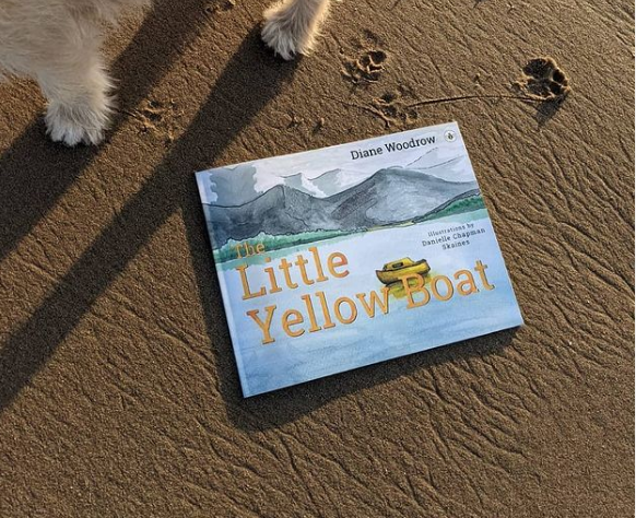 The Little Yellow Boat book by Diane Woodrow on the sand with small footprints around it.
