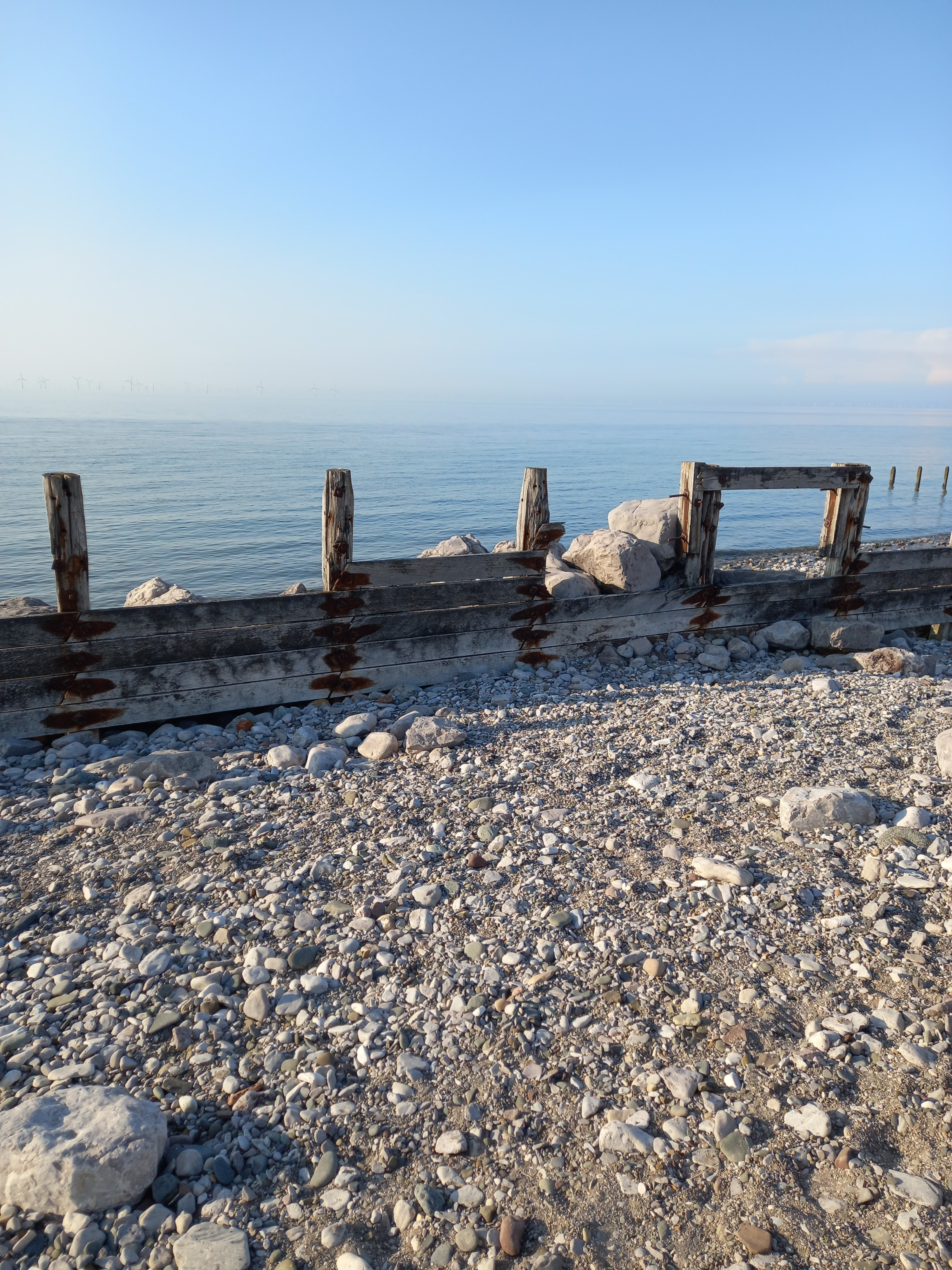 Picture of stoney beach looking out to still clean sea taken by Diane Woodrow author of The Little Yellow Boat book