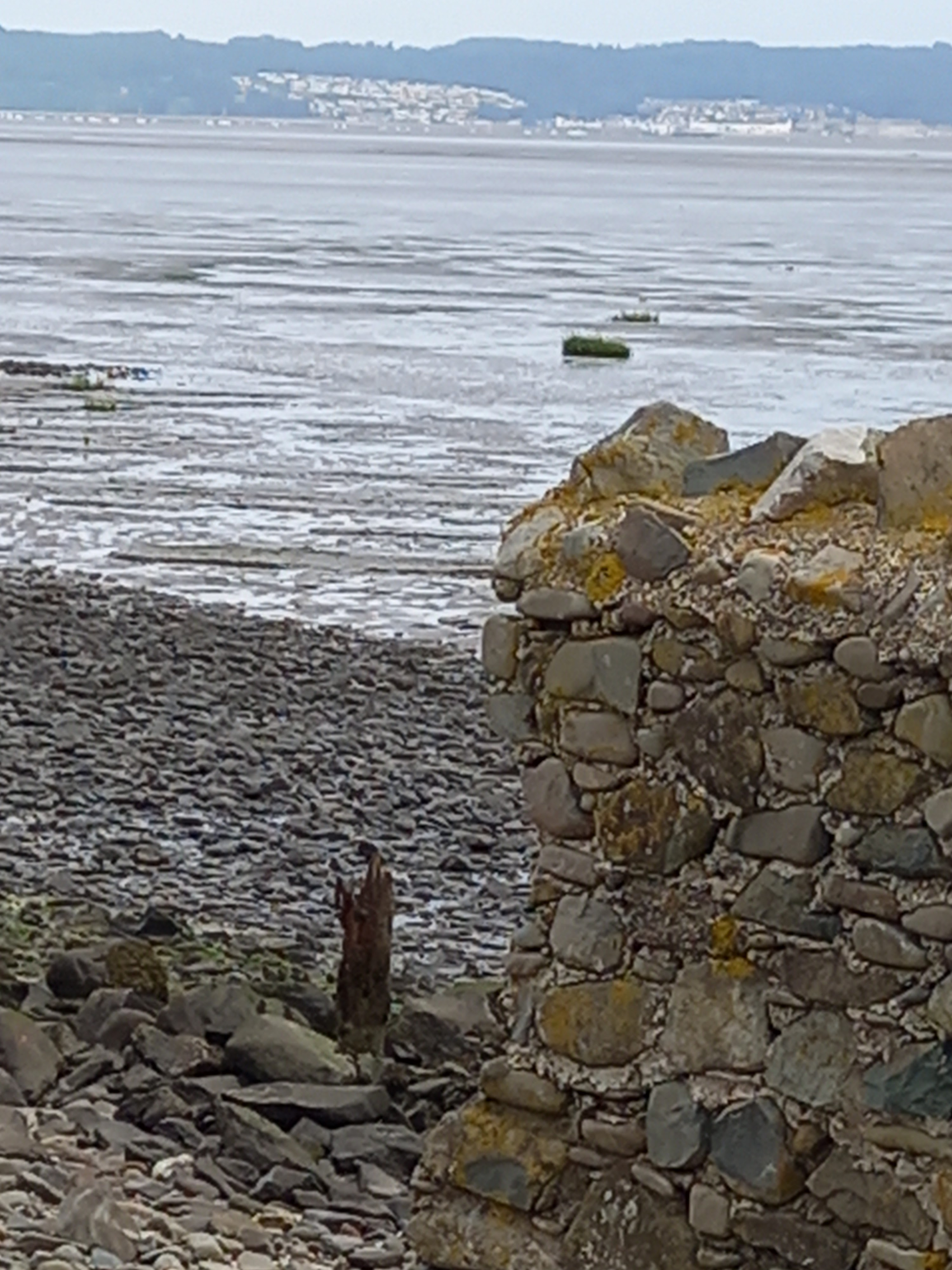 Picture of a broken wall and pebbled beach looking across water to a town and island. Taken by Diane Woodrow
